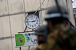 Member of Japan's Self Defense Forces march past a clock that has stopped at the time of the earthquake as they make their way from a search for survivors and victims of the quake in Ishinomaki, Miyagi Prefecture, Japan on 14 March 2011. .Photographer: Robert Gilhooly