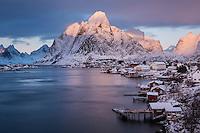 Dramatic winter sunrise on Olstind and Reine, Moskenesøy, Lofoten Islands, Norway