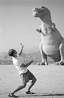 man acting scared by a large dinosaur in the California desert