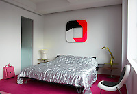 A silver bedcover tones down the brightness of the pink carpet in the bedroom of Karim Rashid's New York apartment