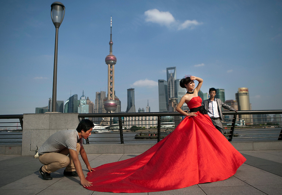 A woman in a red gown gets wedding portraits taken on the Bund, with the skyscrapers of Pudong looming in the background.
