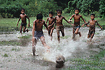 Boys playing soccer in the  flooded pastures, Sylhet, Bangladesh, 1983<br />