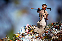 An illegal migrant boy from Myanmar collects plastic at a rubbish dump site near Mae Sot December 22, 2009. Despite terrible living condition and the fear from being send back to their country, several hundreds illegal migrants from Myanmar live and earn average one US dollar per day collecting plastic at the rubbish dump near the border town of Mae Sot. Myanmar's long standing political crisis has forced millions of people across the border for a better and safer life. The first refugees arrived and set up camps in the Myamar-Thailand border in 1984. Now there are over 140,000 refugees in nine official camps along Thailand's western border. Many more are expected to be in unofficial settlements.  REUTERS/Damir Sagolj (THAILAND)