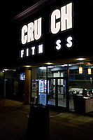 Crunch Fitness storefront with missing letters in illuminated sign.