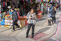A woman texts on her smartphone in Chinatown in New York during the Chinese New Year celebration on Saturday, February 20, 2016. (© Richard B. Levine)