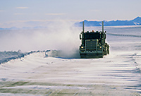 Semi travels the Dalton highway during high winds and blowing snow, north of the Brooks Mountain Range, on Alaska's Arctic Coastal Plains.