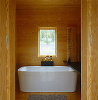 Warm Southern yellow pine has been used to line the walls of this contemporary bathroom in a modern log cabin