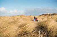 Woman walks through high dune grass, Berneray, Outer Hebrides, Scotland