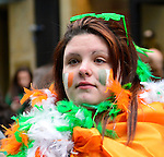 March 16, 2013 - New York, NY, U.S. - Closeup of woman dressed in oragne, green and yellow feathers, while watching the 252nd annual NYC St. Patrick's Day Parade.