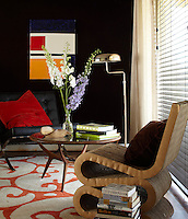 In a corner of the master bedroom a black wall displays an abstract painting by Nacho Figueras and creates an effective backdrop for a pair of chairs by Mies van der Rohe  and Frank Gehry
