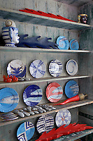Hand-painted plates are displayed with other objects and finds on a distressed bookshelf in the living room