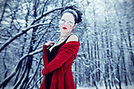 A young girl with pale skin and black hair dressed in red and black standing in a snowy forest.