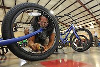 NWA Democrat-Gazette/ANDY SHUPE<br /> May Clevenger, a parent and volunteer, inflates a tire on a bike Friday, Sept. 11, 2015, while assembling a bicycle at John Tyson Elementary School in Springdale. Volunteers assembled the last 32 bikes of a total 850 bikes funded by a grant from the Walton Family Foundation.