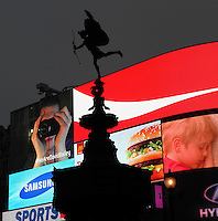 Anteros figure silhouetted against floodlit adverts panels, Piccadilly Circus, London, UK. The statue of the nude winged archer, at the top of The Shaftesbury Monument Memorial Fountain, is known as Eros Column, 1892-1893, aluminium cast, by Alfred Gilbert. Picture by Manuel Cohen.