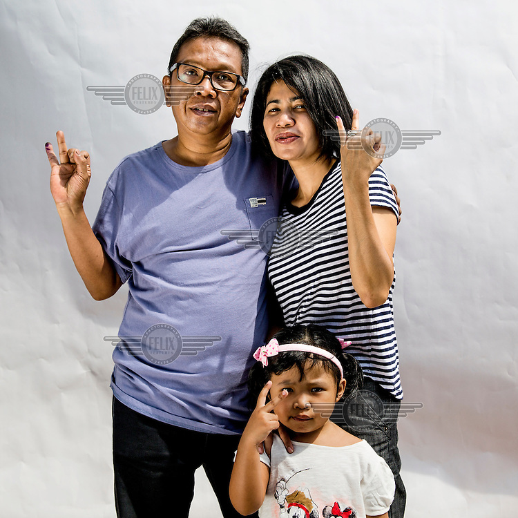A family flash a two fingered sign, symbolising Indonesian presidential candidate Jokowi's candidacy number after the parents cast their votes at a polling station in Jakarta.