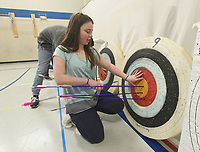 NWA Democrat-Gazette/FLIP PUTTHOFF <br /> ON TARGET<br /> Gabby Roe pulls her arrows from the target Wednesday March 15 2017 during archery competition in Deb Walter's physical education class at Rogers New Tech High School. Students took part in a bull's eye contest and Roe was one of the top shooters. She shot five bull's eyes midway through the class and was aiming for more.