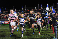 George Ford of Bath Rugby, mascots in hand, leads his team out onto the field. European Rugby Challenge Cup match, between Bath Rugby and Cardiff Blues on December 15, 2016 at the Recreation Ground in Bath, England. Photo by: Patrick Khachfe / Onside Images