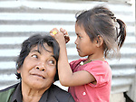 A girl picks lice from the hair of her mother in the Phnom Penh neighborhood of Sen Rikreay. Many people in this community are infected or affected by HIV and AIDS.