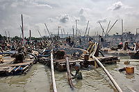 Indonesia - Bangka Island - Outskirts of Sungai Liat - Thousands of miners scratching the lake bed looking for tin. Makeshift pontoons are floating on the water, bamboo sticks are used to scratch the bed and plastic pipes suck the black gold and pump it to the surface. Miners work from 8am until 5 pm surrounded by the undearable noise and black smoke provoked by the engines used to pump the black gold. They earn 15US$ per day. At least one miner die every week.