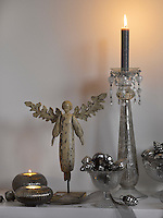 A Christmas still life with a wooden angel, tealights in silver glass holders and a silver candlestick