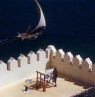 A chair on the castellated roof terrace is momentarily abandoned as a local dhow heads out to sea for a night's fishing