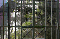 Exterior of the Plant History Glasshouse (formerly Australian Glasshouse), 1830s, Rohault de Fleury, Jardin des Plantes, Museum National d'Histoire Naturelle, Paris, France. Detail of the glass and metal wall which is reflecting the New Caledonia Glasshouse (formerly The Mexican Hothouse), 1834-36, Rohault de Fleury. Through the windows may be seen the luxuriant vegetation.