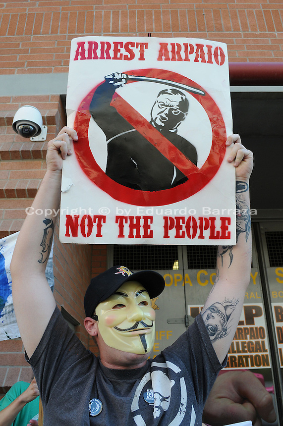 Phoenix, Arizona. September 17, 2012 - A small crowd of demonstrators in Phoenix, Arizona gathered to mark one year since the beginning of the Occupy Movement that opposes Wall Street and large corporations that represent the one percent who control wealth in the United States. In this photograph, a man wearing an 'Anonymous' mask protests outside the Fourth Avenue Maricopa County Jail -located in downtown Phoenix. The man was part of the Occupy Phoenix group. Photo by Eduardo Barraza © 2012