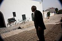 Tunisia dopo la rivoluzione: un anziano elegante di profilo in una strada di Sidi Bouzid. Una casa bianca con un tavolino verde di fronte.<br /> <br /> TUNISIA after spring revolution
