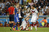 Bastian Schweinsteiger of Germany is helped off the ground by Mesut Ozil