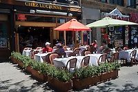 Patrons sit at the outdoor cafe of Chez Lucienne restaurant on Lenox Avenue in the neighborhood of Harlem in New York on Saturday, June 23, 2012. Wide sidewalks and a renaissance in Harlem have caused a number of restaurants to open catering to the more upwardly mobile newer residents. (© Richard B. Levine)