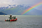 A United States Coast Guard vessel patrols Alaska's Prince William Sound as it travels toward a brilliant rainbow.