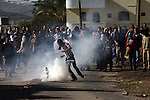 A Palestinian protester kicks a tear gas canister at  Israeli soldiers on the sidelines of a demonstration against the expropriations by Israel in the West Bank village of Kafr Qaddum, near Nablus, on November 30, 2012. Photo by Nedal Eshtayah