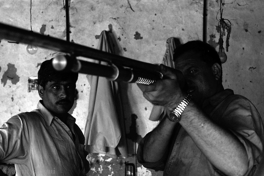 a weapon near completion is checked by a master technitian.  darra adam khel, tribal areas, pakistan.  september 2003&amp;#xA;&amp;#xA;copyright asim rafiqui 2003<br />