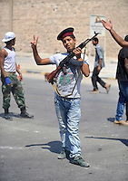 A boy stands with a gun at a checkpoint on a street in Tripoli. As soon as the rebel offensive gained steam, the population of Tripoli took up arms and took to the streets to defend their neighbourhoods and take on Gaddafi loyalists. After a six month revolution, rebel forces finally managed to break into Tripoli and have taken control of Bab al-Aziziyah, Col Gaddafi's compound and residence. Few remain that are loyal to Gaddafi in the city; it is seeming that the 42 year regime has come to an end. Gaddafi is currently on the run.
