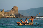 Young fishers return to shore in a traditional outrigger canoe, laughing and playing. Sepi Beach, Lombok, Indonesia