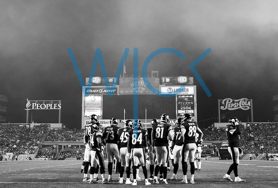 Ben Roethlisberger #7, Antonio Brown #84, Jesse James #81, Matt Spaeth #89, and other members of the Pittsburgh Steelers huddle up as smoke from fireworks lingers in the first quarter against the Indianapolis Colts during the game at Heinz Field on December 6, 2015 in Pittsburgh, Pennsylvania. (Photo by Jared Wickerham/DKPittsburghSports)