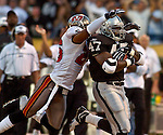 Tampa Bay Buccaneers defensive back Dwight Smith (26) attempts to stop Oakland Raiders running back Tyrone Wheatley (47) on Sunday, September 26, 2004, in Oakland, California. The Raiders defeated the Buccaneers 30-20.