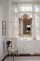 Unusually, in this bathroom an antique mirror hangs in front of the Venetian blinds