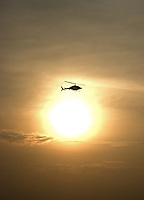 A helicopter flies over the golden sphere of the sun in partly cloudy morning sky.