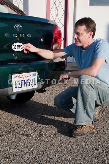 Mid adult man placing a 38 miles per gallon fuel efficiency bumper sticker ...