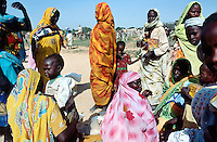 Sudan. West Darfur. Kerenek. A group of women, wearing colorful veils on the heads, and their children after the food distribution organised by the non-governmental organization (ngo) Médecins sans Frontières (MSF) Switzerland. © 2004 Didier Ruef /