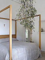 A large olive branch hanging around a pendant light makes an unusual chandelier in this bedroom with a monastic feel