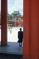 The silhouette of a visitor adds to the mystery of the large orange wooden temples at the Heian Shrine complex in Kyoto.