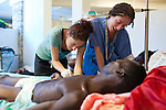 Project HOPE volunteer nurses Jane, left, and Jill Caporiccio, who are sisters, treat a cholera patient at the Hospital Albert Schweitzer on Thursday, October 28, 2010 in Deschapelles, Haiti.