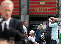 (Oslo July 26, 2011)  Two friends embrace in the background as party secretary Raymond Johansen (Laubor) talk to press following the terrorist attacks...A large vehicle bomb was detonated near the offices of Norwegian Prime Minister Jens Stoltenberg on 22 July 2011. .Another terrorist attack took place shortly afterwards, where a man killed 68 people, mainly children and youths attending a political camp at Utøya island. ..Anders Behring Breivik was arrested on the island and has admitted to carrying out both attacks..(photo:Fredrik Naumann/Felix Features)