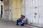 Palestinians sit a closed shops during a general strike in support of Palestinian prisoners on hunger strike in Israeli jails, in the old market of the West Bank city of Nablus April 27, 2017. Photo by Ayman Ameen