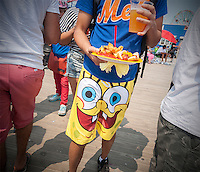 A visitor to Coney Island in his beach attire on Sunday, July 5, 2015 with his plate of Nathan's hot dogs and fries, in Brooklyn in New York over the 4th of July weekend.   (© Richard B. Levine)
