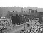 Pittsburgh PA:  View of the point area prior to the Gateway Center construction - 1949.  Eppy's parking lot at Liberty Avenue and Fourth Avenue in Pittsburgh.  Pittsburgh Press Building in the background.  Company signs on the city buildings include:  Esser Costume Company, Amaco Service Station, and Follansbee Steel Corporation