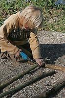 Kinder basteln Klangspiel aus Ästen, Junge sägt Äste auf richtige Länge