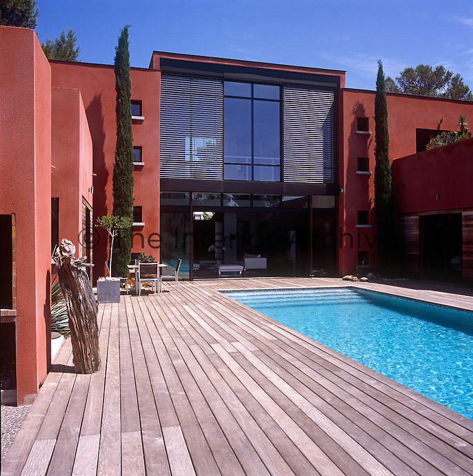 The exterior of a modern villa in red stone. A table and chairs stand on a decked terrace beside a swimming pool.